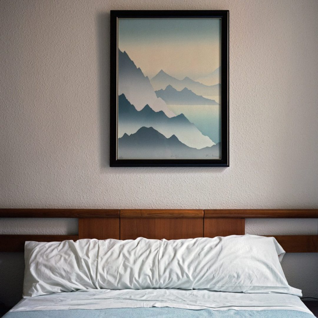 Surf resort with white bedding and beautiful picture above the bed