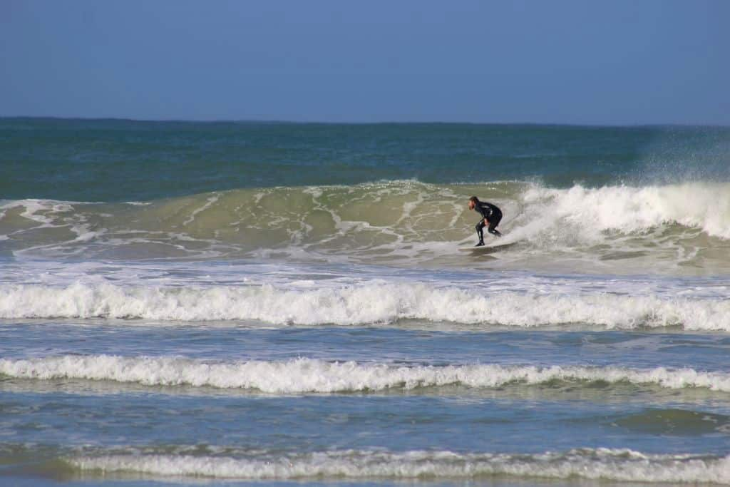Intermediate surfer catching a wave on a surf trip in South Africa.